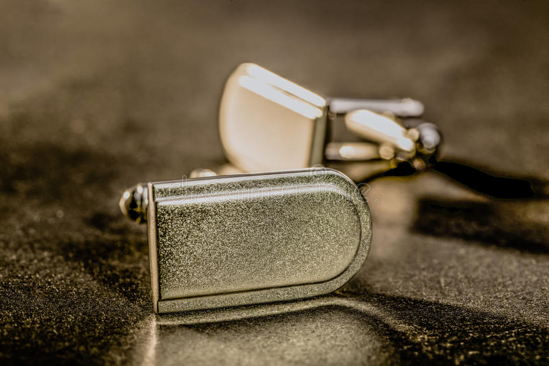 Cuff Links. A pair of cuff links lie together in low warm light on a dark surface stock images