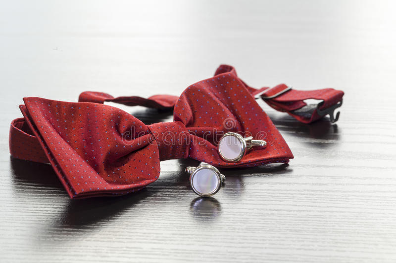 Cuff links and red bow tie. Silver cuff links and red bow tie stock photography