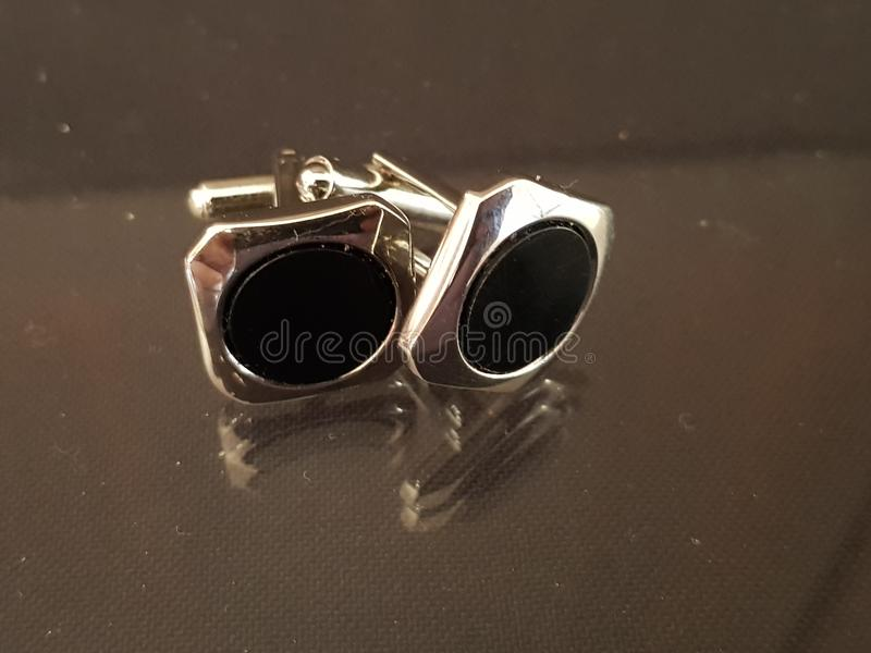 Cuff links. On reflective background macro shot black silver stock photography
