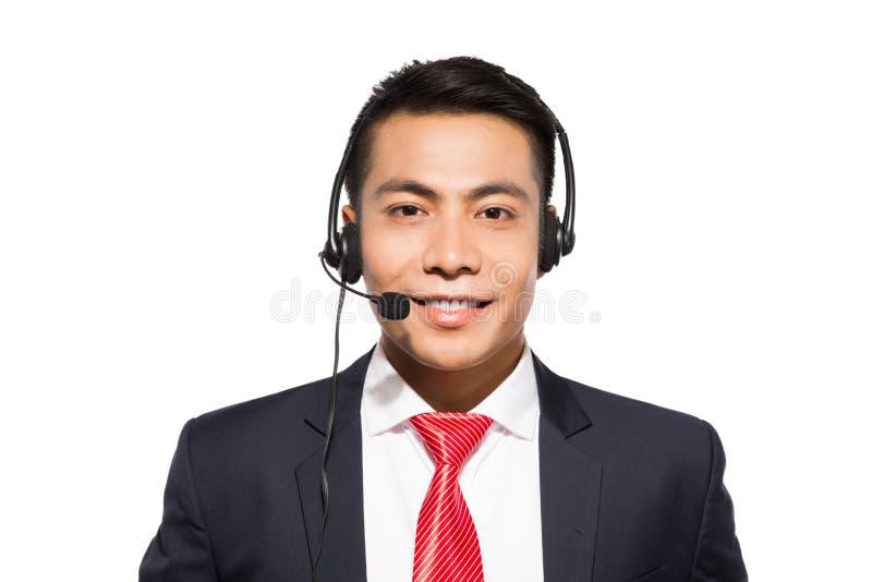 Cuffia avricolare d'uso del giovane uomo d'affari asiatico, colpo dello studio fotografia stock