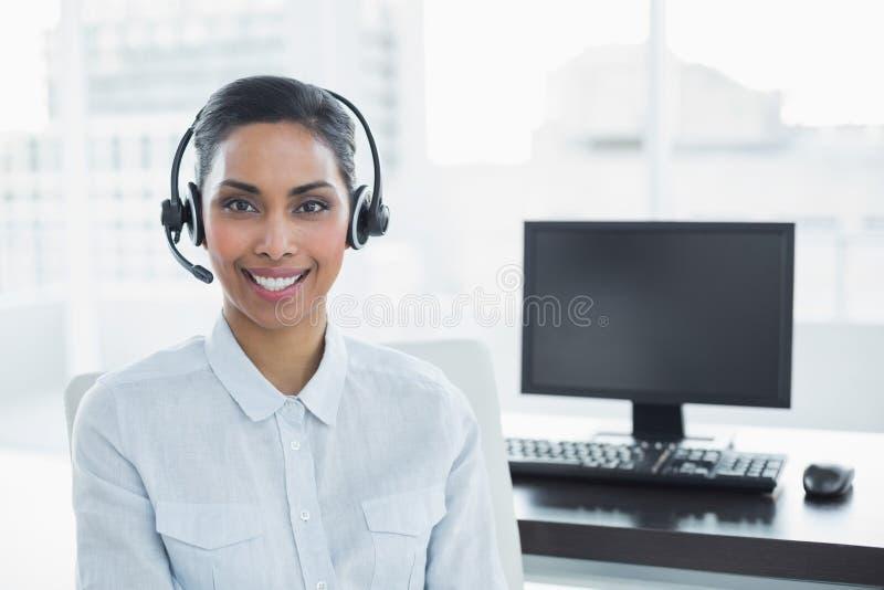 Cuffia avricolare d'uso dell'agente femminile attraente che sorride alla macchina fotografica immagini stock