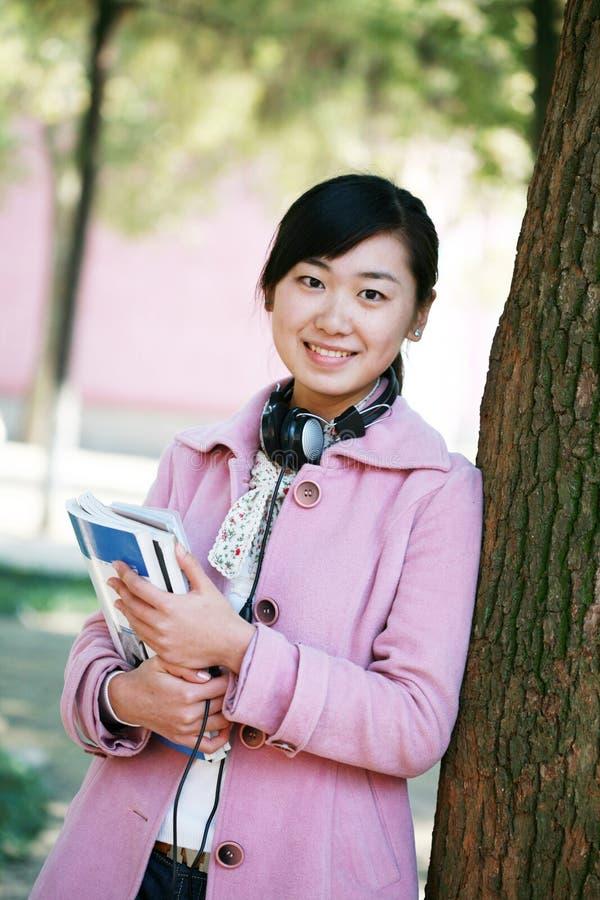 Cuffia avricolare e libro della stretta della ragazza fotografie stock libere da diritti