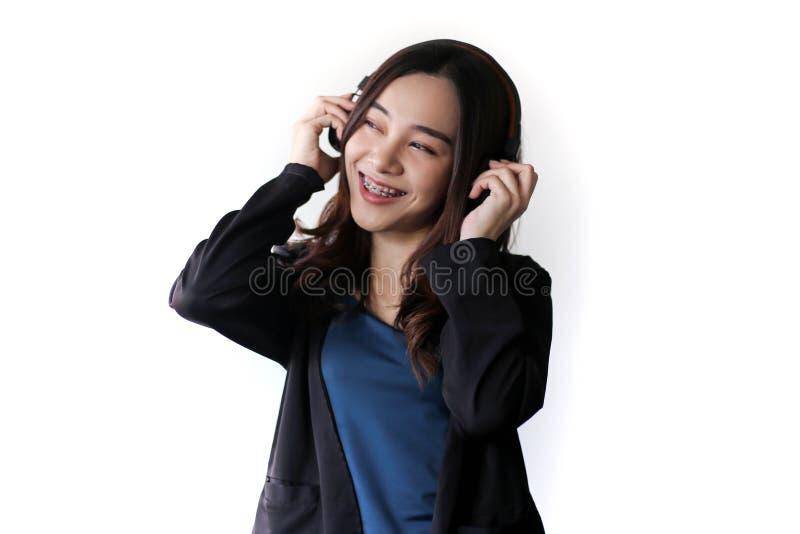 Cuffia d'uso della bella donna asiatica graziosa e musica d'ascolto su fondo bianco fotografia stock