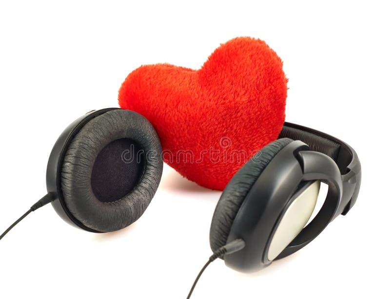 Cuffie accanto ad una composizione rossa nel cuore immagini stock libere da diritti