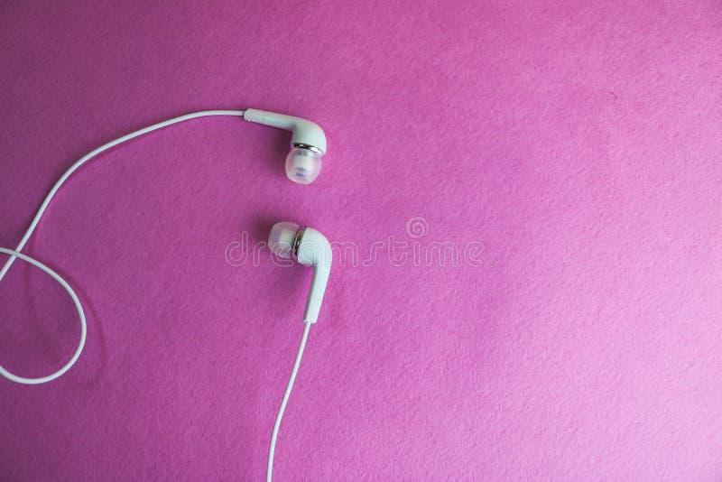 Cuffie bianche di bello vuoto di plastica digitale moderno con i cavi per ascoltare la musica su un fondo rosa porpora Copi lo sp fotografia stock libera da diritti
