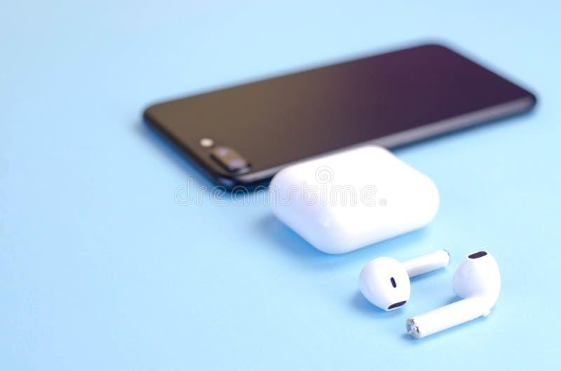 Cuffie bianche senza fili con uno smartphone su un fondo blu fotografia stock