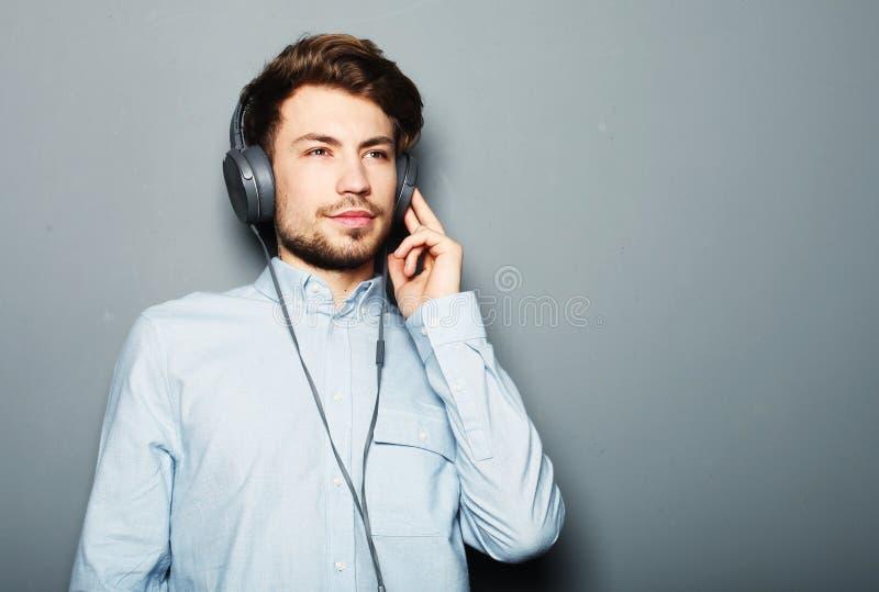 Cuffie d'uso belle del giovane ed ascoltare la musica fotografia stock libera da diritti