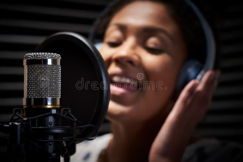 Cuffie d'uso del vocalist femminile che cantano nel microfono in studio di registrazione fotografie stock libere da diritti