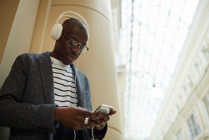 Cuffie d'uso dell'uomo africano d'avanguardia fotografia stock