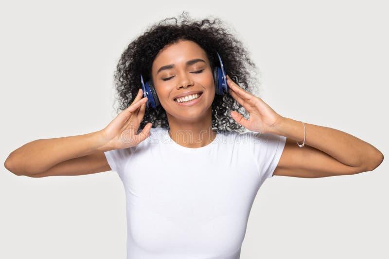 Cuffie d'uso della donna africana del ritratto di colpo in testa godere della musica favorita immagine stock libera da diritti