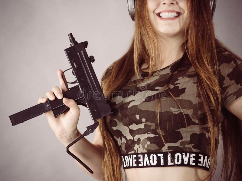 Cuffie d'uso della donna che tengono pistola fotografia stock libera da diritti