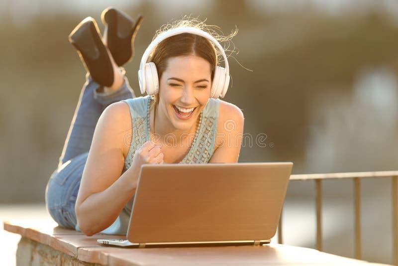 Cuffie d'uso della ragazza emozionante che guardano media sul computer portatile fotografia stock libera da diritti