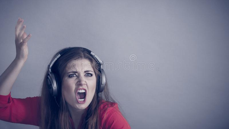 Cuffie d'uso di gioco della donna arrabbiata fotografia stock libera da diritti
