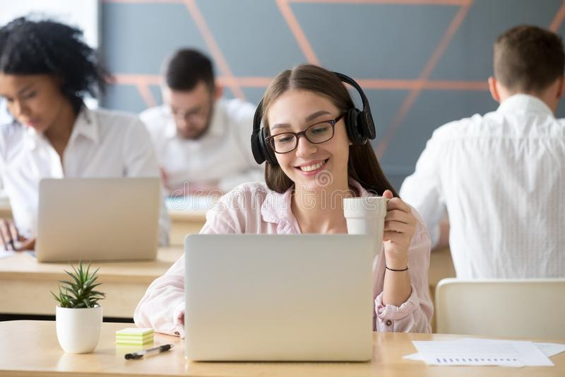 Cuffie d'uso sorridenti della donna che guardano video online durante il co immagine stock libera da diritti