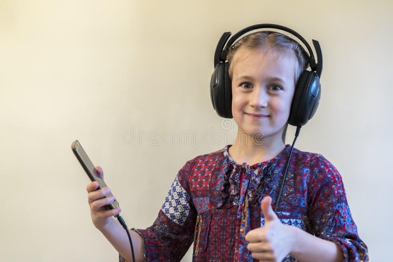 Cuffie della bambina facendo uso del telefono Pollici in su immagini stock