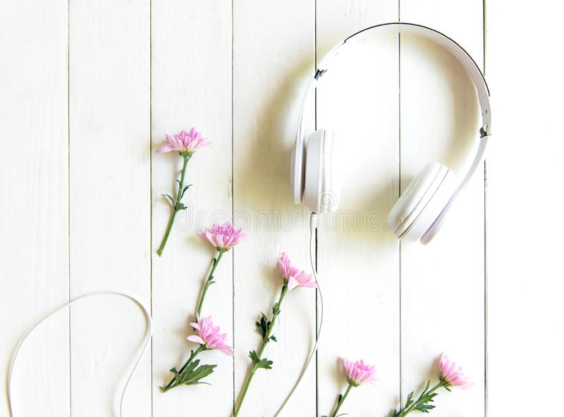 Cuffie di vista superiore sullo scrittorio bianco con area rosa del copyspace e del fiore per un testo fotografia stock libera da diritti