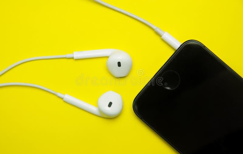 Download Cuffie e cellulare bianchi fotografia stock. Immagine di apparecchiatura - 56888620