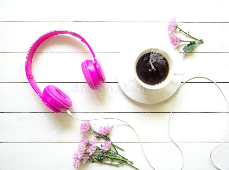 Cuffie e tazza di caffè rosa sulla tavola di legno dello scrittorio con il fiore rosa Concetto di stile di vita e di musica Vista immagine stock