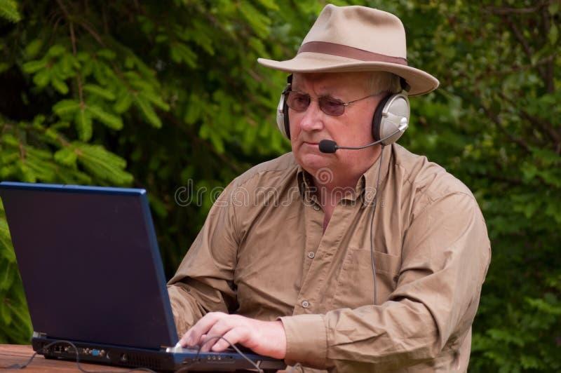 Cuffie maschii dell'anziano del computer portatile fotografia stock