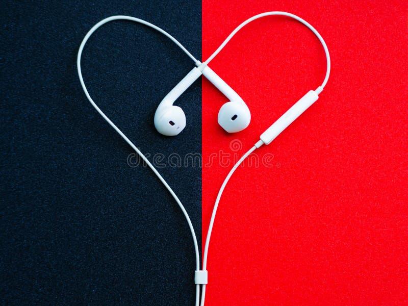 Cuffie metalliche bianche, cuffia avricolare in forma di cuore su un fondo nero-rosso immagini stock libere da diritti