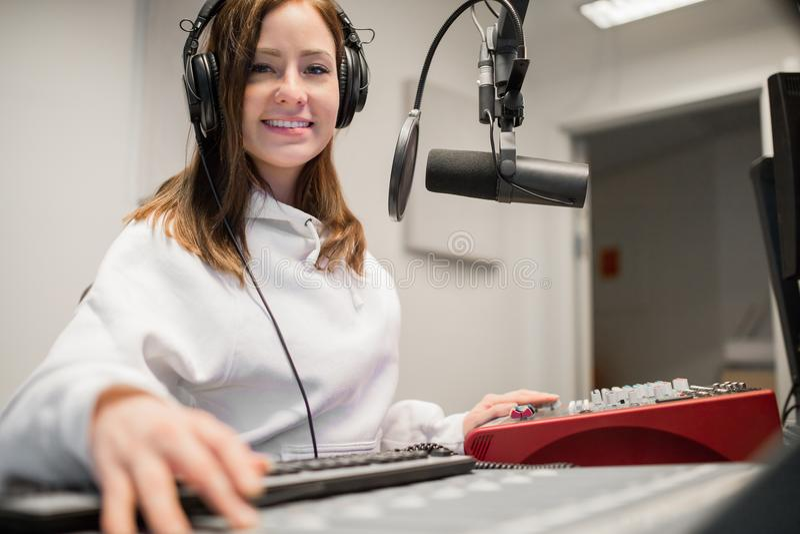 Cuffie radiofoniche di Smiling While Wearing della puleggia tenditrice in studio immagini stock libere da diritti
