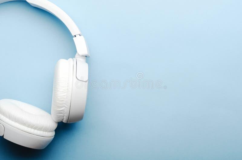 Cuffie senza fili sopraelevate bianche del bluetooth su un fondo blu Primo piano, spazio della copia, vista superiore, flatlay fotografia stock libera da diritti