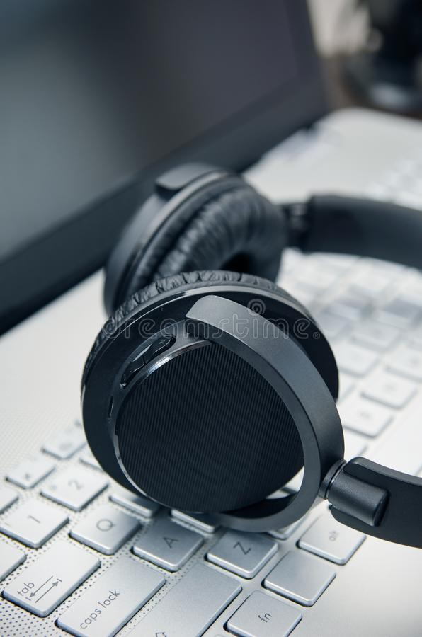 Cuffie senza fili sulla tastiera del computer portatile fotografia stock libera da diritti