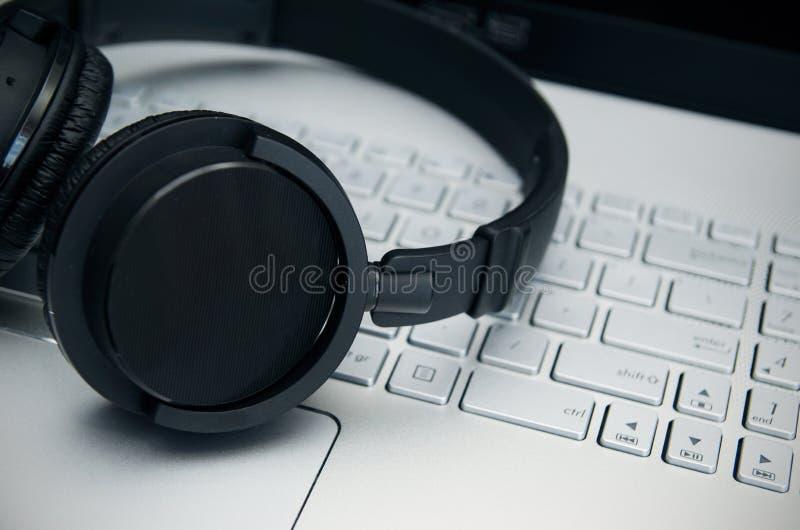 Cuffie senza fili sulla tastiera del computer portatile immagine stock