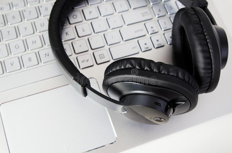 Cuffie senza fili sulla tastiera del computer portatile Musica e concetto di gioco immagini stock