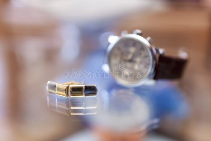Cufflinks och armbandsur arkivfoto
