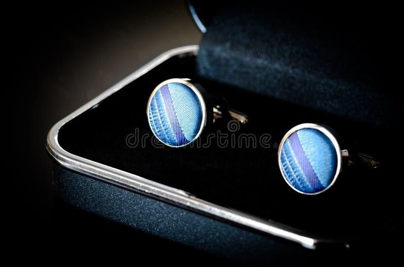 Cufflinks. Old blue cufflinks on black box royalty free stock image