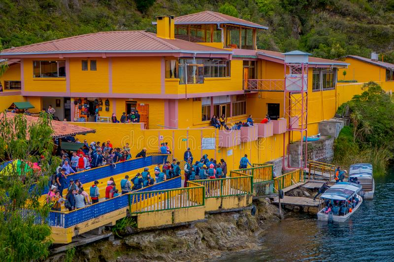 CUICOCHA, ECUADOR, NOVEMBER 06, 2018: Above view of yellow information building with some tourists boarding a boat to royalty free stock photos