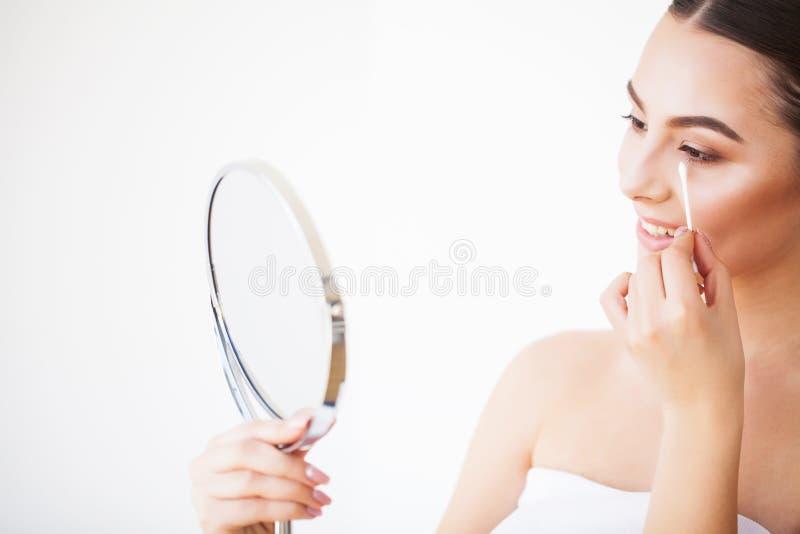Cuidado da cara da beleza Menina com a pele saud?vel que olha no espelho fotos de stock