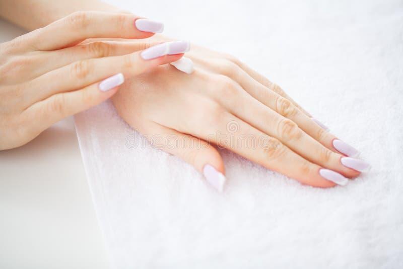 Cuidado da mão e do prego As mãos bonitas do ` s das mulheres com tratamento de mãos perfeito aplicam o creme às mãos da pele Tra imagem de stock