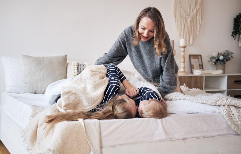 Cuidado da matriz Mãe nova que cobre crianças com uma cobertura no quarto Irmão e irmã que abraçam e que dormem na cama fotografia de stock
