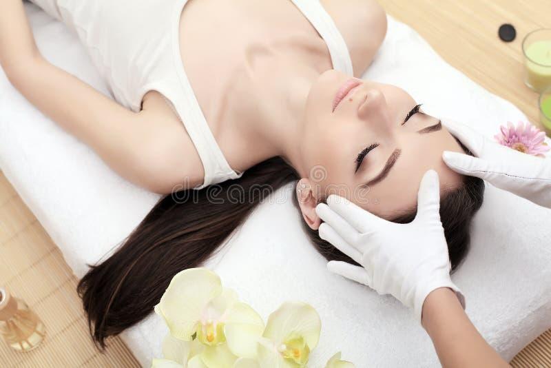 Cuidado da pele e do corpo Close-up de uma jovem mulher que obtém o tratamento dos termas no salão de beleza Massagem de cara dos fotografia de stock