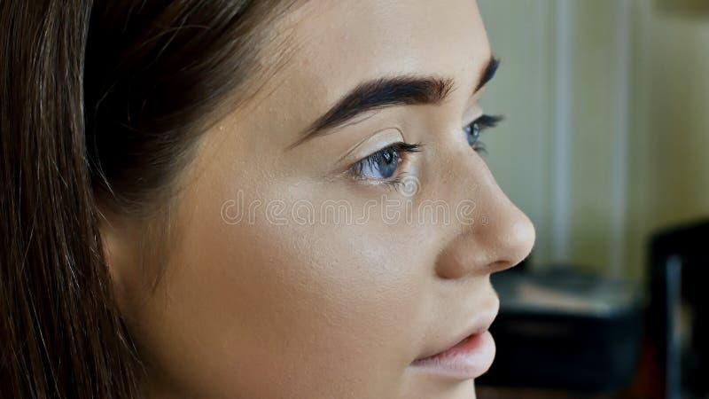 Cuidado das sobrancelhas O close up dos olhos azuis bonitos da mulher, aperfeiçoa a testa dada forma, pestanas longas com composi foto de stock