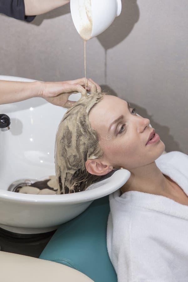 Cuidado de la belleza del pelo, uso de la crema hidratante, peluquero, máscara del pelo de una chica joven hermosa, natural, de l fotografía de archivo