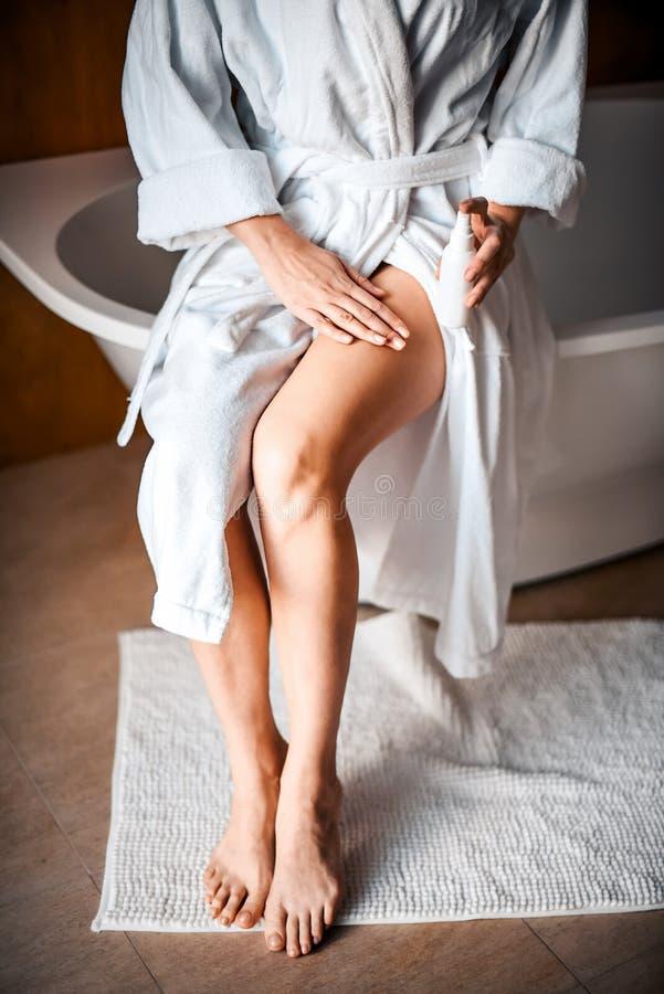 Cuidado de la carrocería Una mujer joven en el cuarto de baño aplica la crema natural a sus piernas cuidado de las Anti-celulitis fotos de archivo libres de regalías
