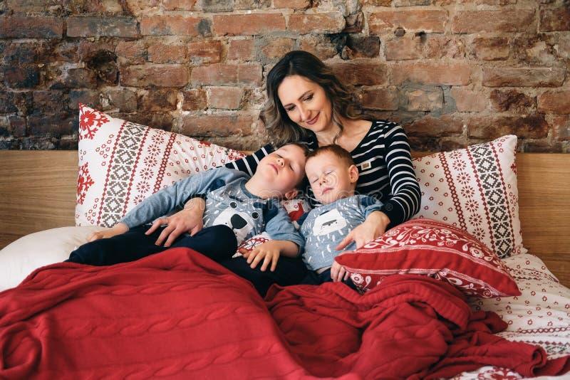 Cuidado de la madre sobre sus niños Niños de abrazo de la mamá en una cama imagen de archivo