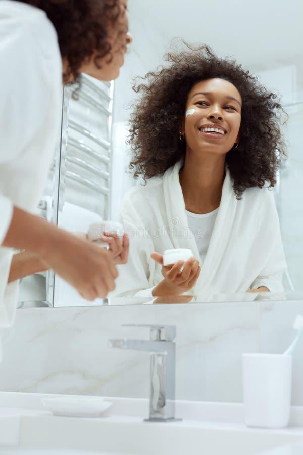 Cuidado de la piel. Mujer aplicando crema facial mirando el espejo del baño imágenes de archivo libres de regalías