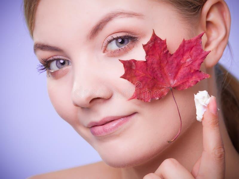 Cuidado de pele Cara da menina da jovem mulher com folha de bordo vermelha imagens de stock