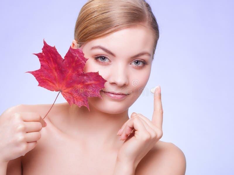 Cuidado de pele Cara da menina da jovem mulher com folha de bordo vermelha fotos de stock royalty free