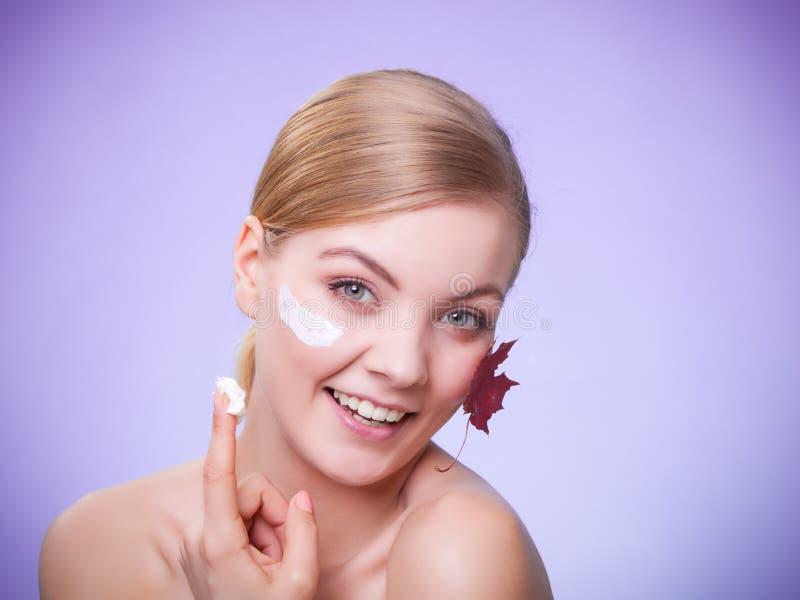 Cuidado de pele Cara da menina da jovem mulher com folha de bordo vermelha imagem de stock