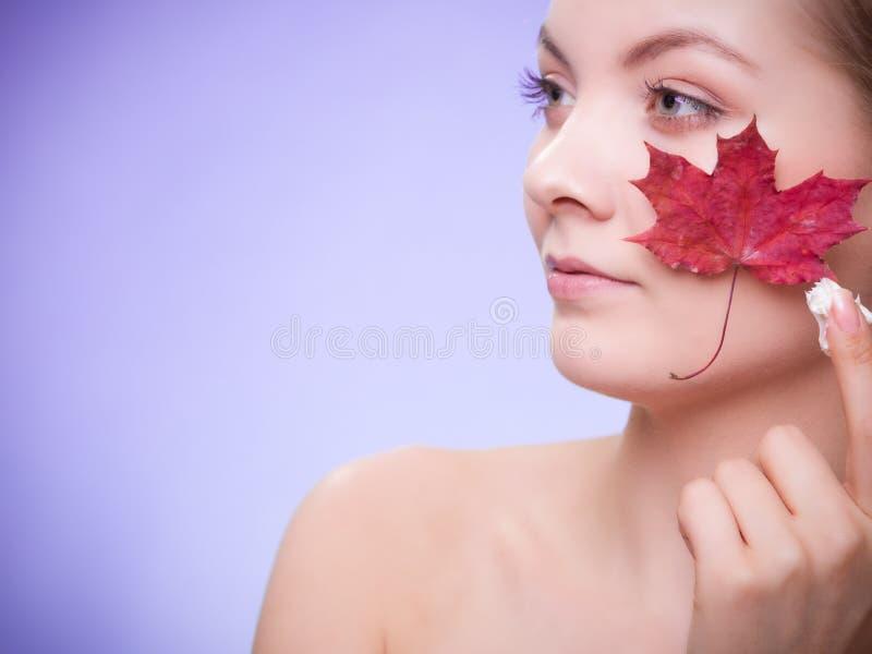 Cuidado de pele Cara da menina da jovem mulher com folha de bordo vermelha imagem de stock royalty free