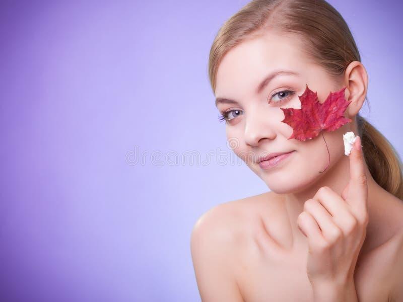 Cuidado de pele Cara da menina da jovem mulher com folha de bordo vermelha fotos de stock