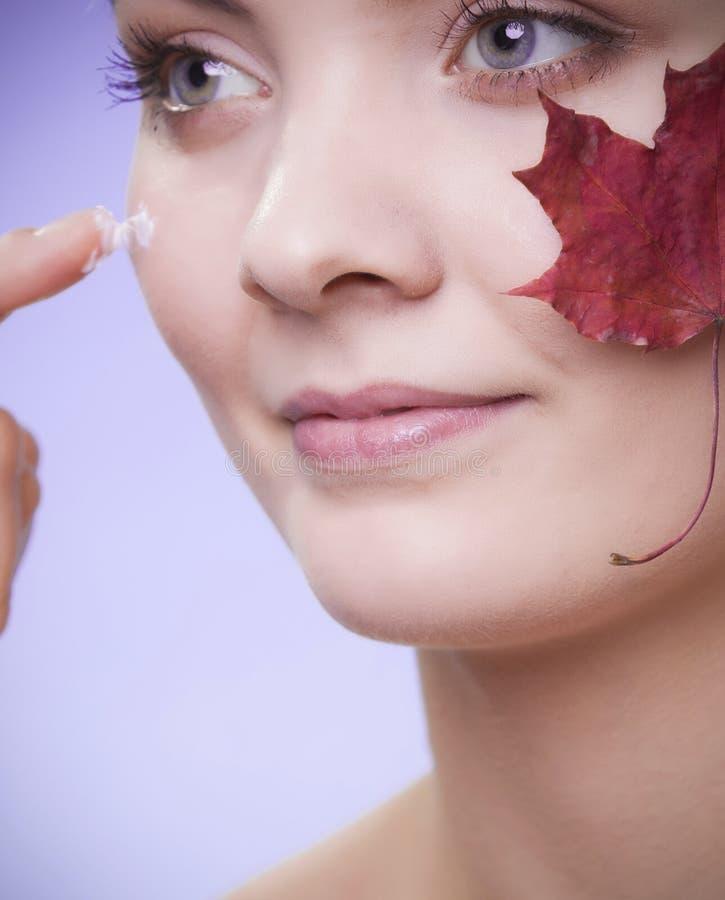 Cuidado de pele Cara da menina da jovem mulher com folha de bordo vermelha foto de stock