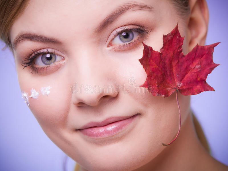 Cuidado de pele Cara da menina da jovem mulher com folha de bordo vermelha fotografia de stock