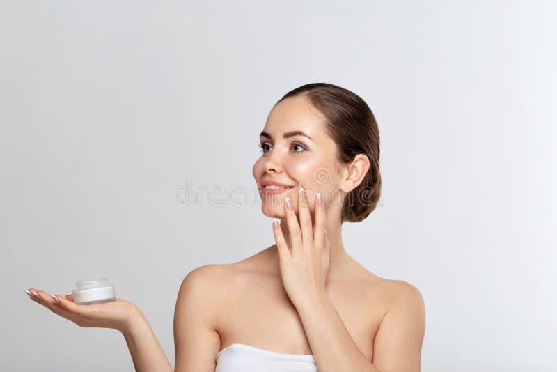 Cuidado de pele Conceito da beleza Jovem mulher que guarda o creme cosm?tico Modelo macio da pele com composição nude imagem de stock royalty free