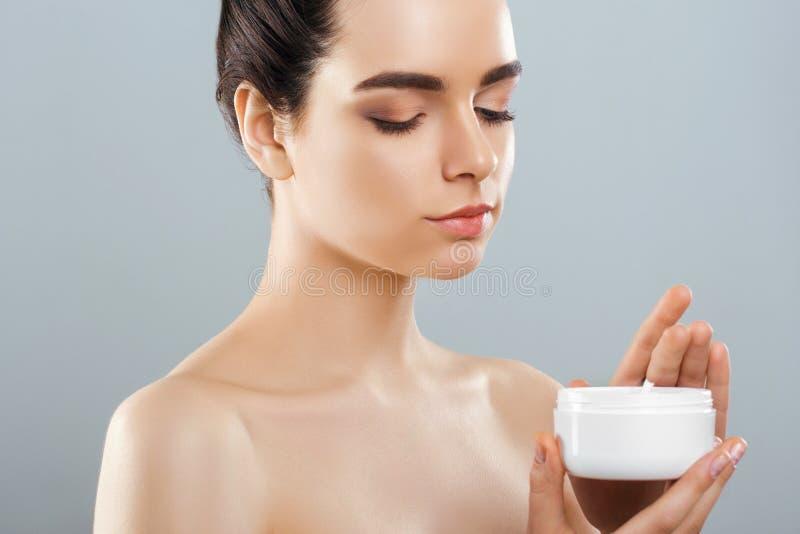 Cuidado de pele Conceito da beleza Mulher bonita nova que guarda o creme cosmético fotos de stock